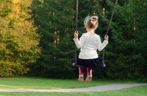 Young girl on a swing with trees in front of her